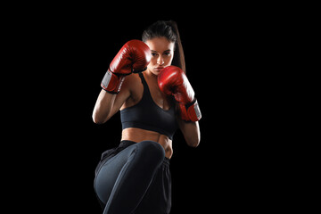 Kickboxing woman in activewear and red kickboxing gloves on black background performing a martial arts kick. Sport exercise, fitness workout.