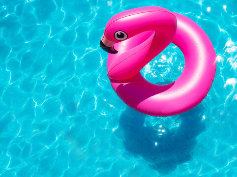 Inflatable flamingo buoy swim in the swimming pool view from above