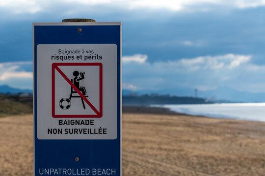 Panneau écrit en Français et en Anglais, signalant une plage non surveillée. Côte atlantique, Anglet, France