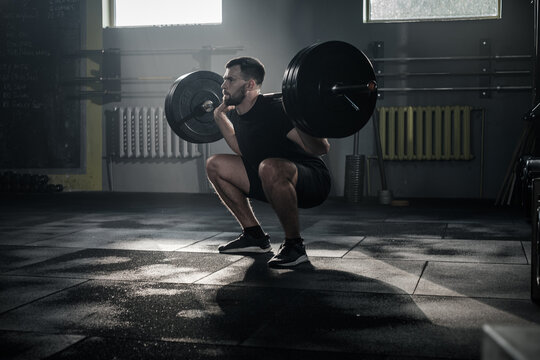 Concentrated Male Do Squat Exercise With Barbell .
