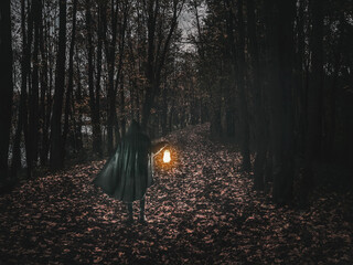 Man in motion in black brilliant hooded cloak holding the glowing lantern on the dark forest