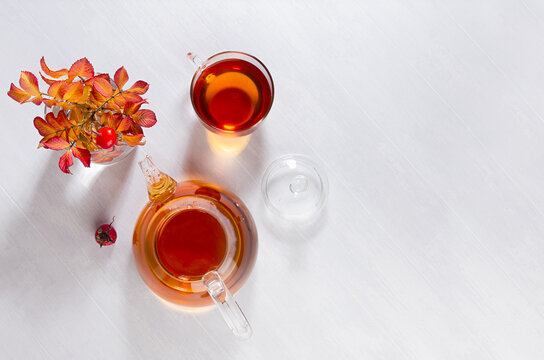 Sunny autumn teatime with rose hip tea with teapot, cup, orange rose hip branch with shadows on white wood table top view, copy space.