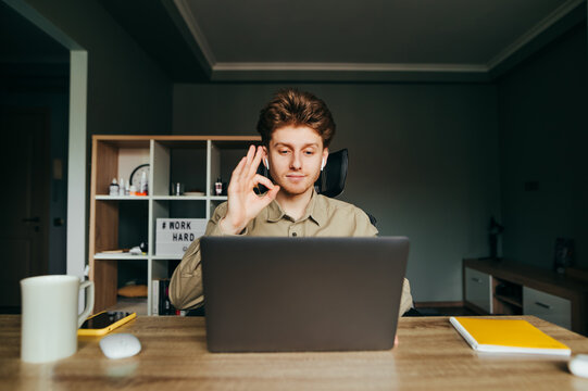 Positive worker in a shirt and headphones on a remote working meeting on a video call, looks at the laptop camera, shows an OK gesture and smiles. Freelancer communicates online with colleagues.
