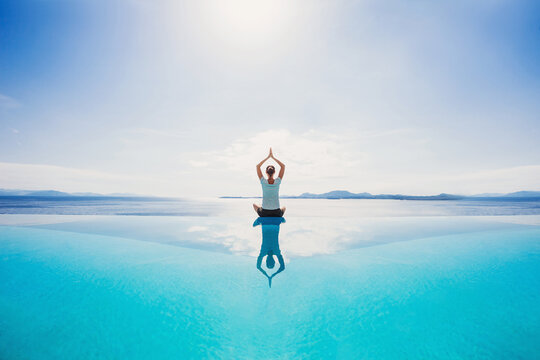 Young woman practicing yoga by the sea. Harmony, meditation, healthy lifestyle and travel concept.