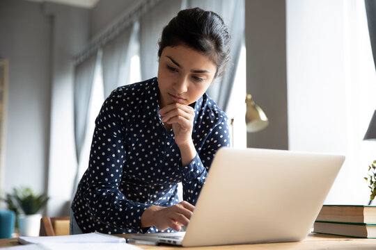 Pensive indian business woman standing in office room standing lean over workplace desk working on laptop thinking about problem solution, create research, do paperwork, corporate task prepare report