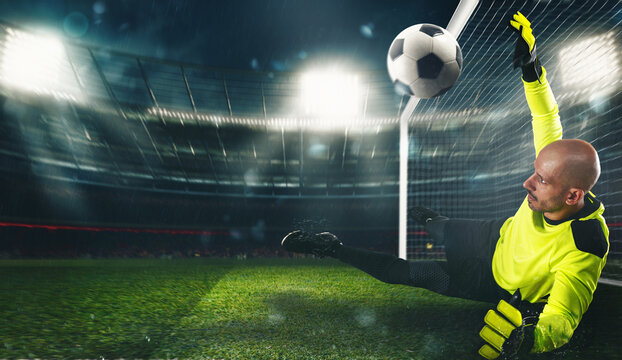Soccer goalkeeper, in fluorescent uniform, that makes a great save and avoids a goal at the stadium