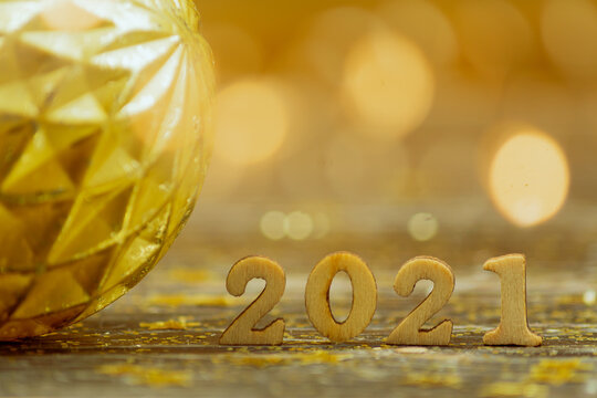 2021 wooden numbers on bokeh background in golden colors. festive greeting card fr new year with copy space.