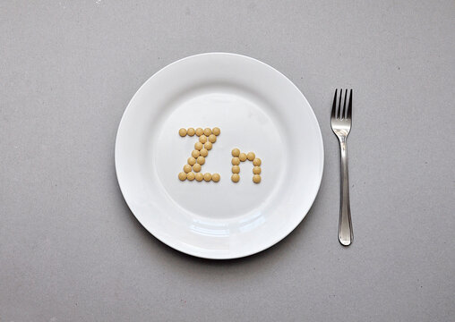 """Sign of the trace element """"zinc"""" from tablets on a white plate. Zinc deficiency in the body"""