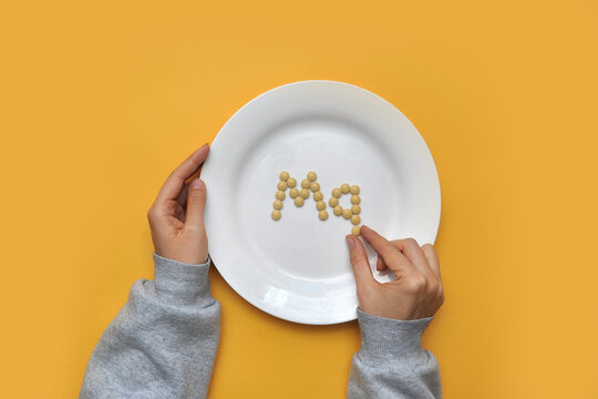 """Sign of the trace element """"magnesium"""" from tablets on a white plate. magnesium deficiency in the body"""