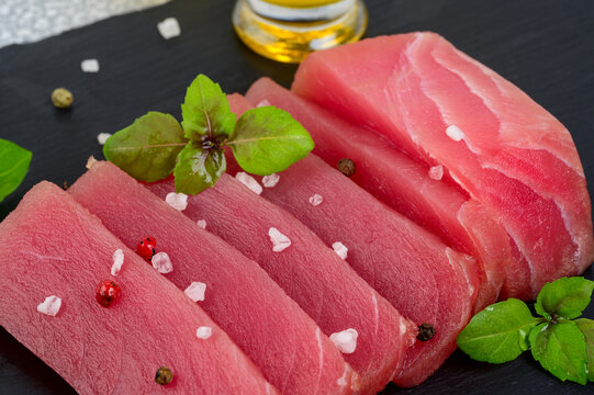 Fresh raw tuna steak with basil. On black rustic background