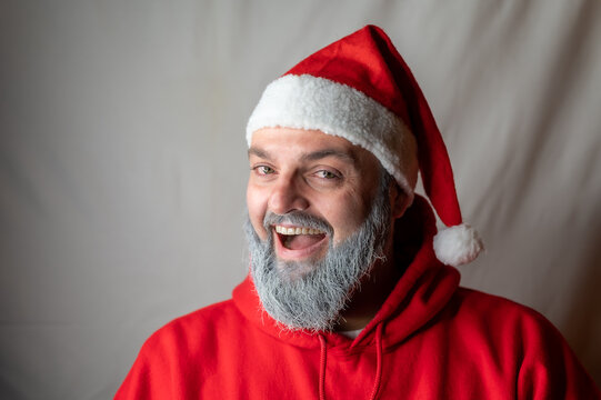 Santa Claus laughs at the camera with his mouth wide open