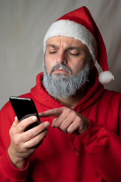 Santa Claus types something on his cell phone and looks suspicious