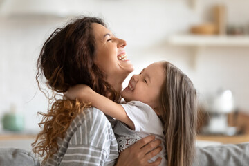 Fototapeta Close up side view overjoyed smiling young mother and daughter hugging and laughing, enjoying tender moment, happy mum and adorable preschool girl kid cuddling, having fun together at home
