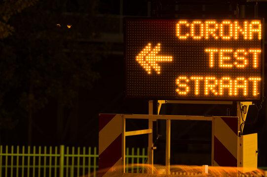 Dutch corona test street information sign ito indicate a test center at night in Arnhem, Netherlands. Translation: teststraat means test street