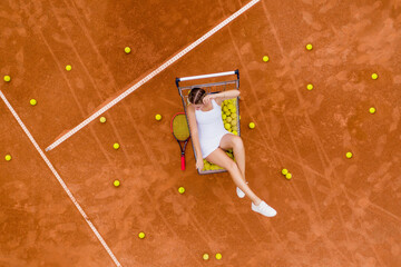 Portrait of smiling woman relaxing on tennis court with a lot of balls and racket after hard tennis trainingg outdoor. Dolly shot. Top view