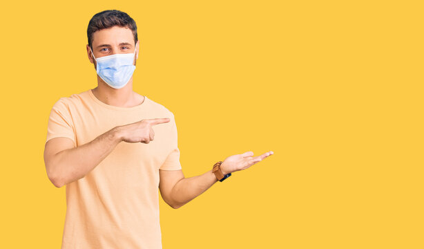Handsome young man with bear wearing medical mask for coronavirus amazed and smiling to the camera while presenting with hand and pointing with finger.