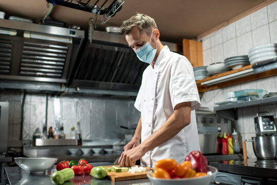 Professional young chef in uniform and protective mask chopping fresh zucchini