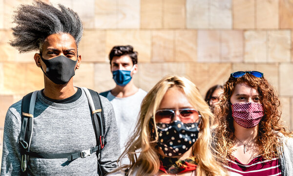 Multiracial crowd walking near wall at city urban context - New normal lifestyle concept with young people covered by protective face mask - Selective focus on left afroamerican guy