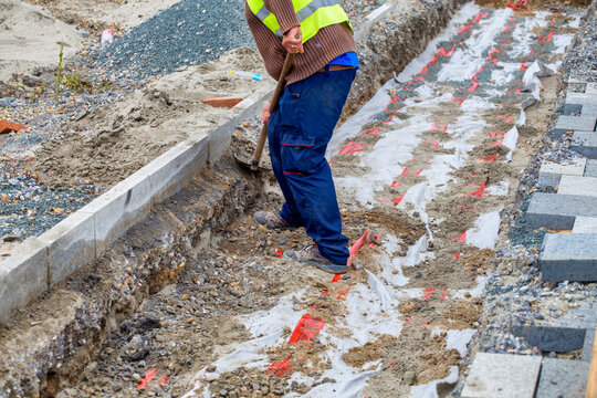 Worker backfilling power cables trenches
