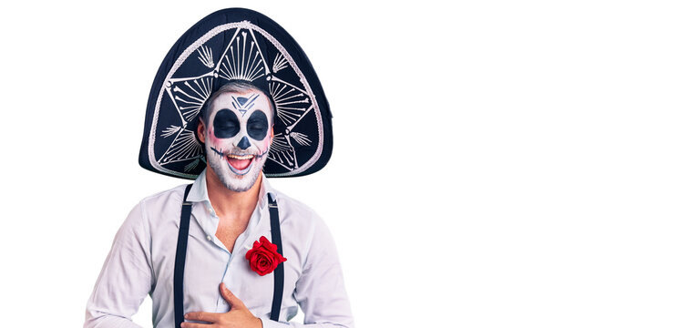 Man wearing day of the dead costume over background smiling and laughing hard out loud because funny crazy joke with hands on body.