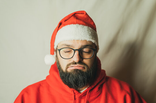 Annoyed man in Christmas hat exhales with closed eyes
