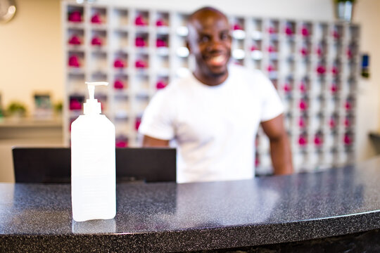 afro american man receptionist sanitizing work surface desk