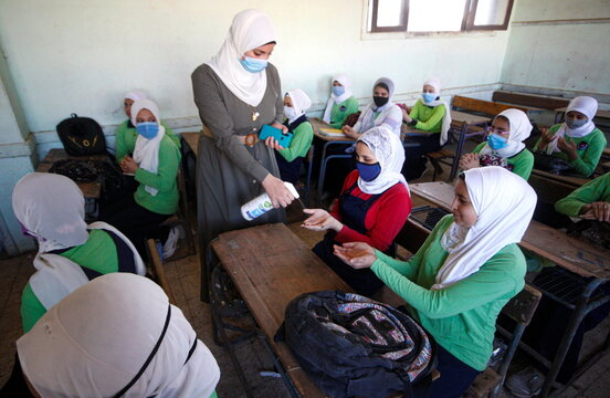 An Egyptian teacher sprays sanitizer on student's hands during the first day's class at El Safa school, following months of closure due to the coronavirus disease (COVID-19) outbreak in the Giza suburb of Awsim