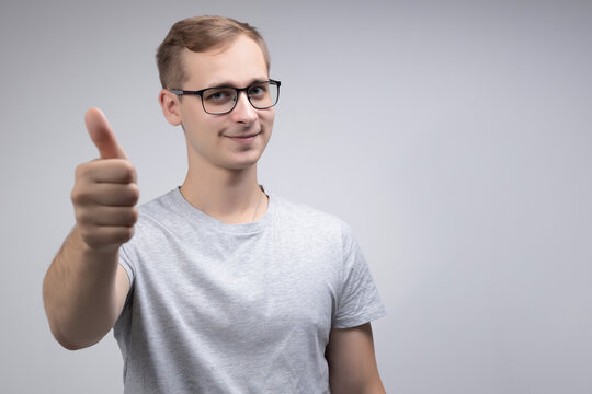 Young handsome skinny guy shows thumbs up isolated on white and grey background. Studio portrait.