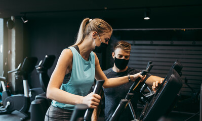 Young fit and attractive woman at body workout in modern gym together with her personal fitness instructor or coach. They wearing protective face masks. Coronavirus world pandemic and sport theme.