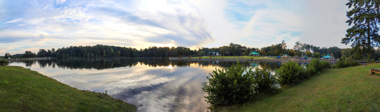 a stunning panoramic shot of a gorgeous sunset, with still blue lake water, lush green trees, blue sky and clouds at Rhodes Jordan Park At Lawrenceville Lake in Lawrenceville Georgia