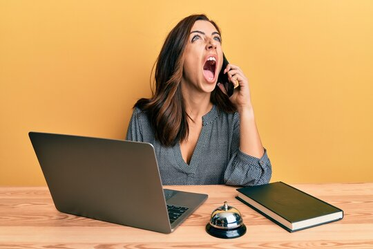 Young brunette woman working at hotel reception talking on the phone angry and mad screaming frustrated and furious, shouting with anger looking up.