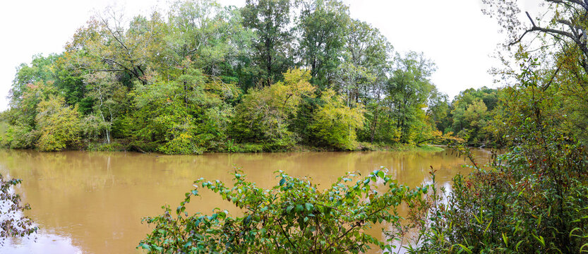 a gorgeous panoramic shot of the deep brown river water and the lush green and autumn colored trees on the banks of the lake at Sweetwater Creek State Park in Lithia Springs Georgia