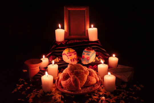 Mexican day of the dead altar with bread and sugar skulls on dark background
