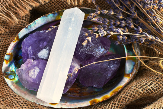 An image of an abalone shell filled with amethyst crystals and white selenite on old burlap textile.