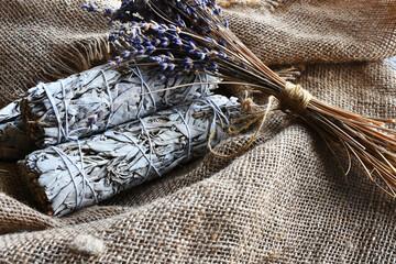 Fototapeta An image of white sage smudge sticks and dried lavender flowers on vintage burlap cloth.  obraz
