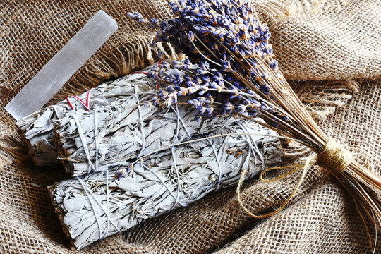 An image of white sage smudge bundles with dried lavender flowers and white selenite on burlap fabric.