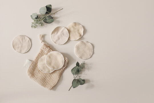 Bio organic cotton reusable round pads for make up removal. Dry eucalyptus branches.and knitted bag. Beige table background. Zero waste concept. Sustainable bathroom and lifestyle. Flat lay, top view.