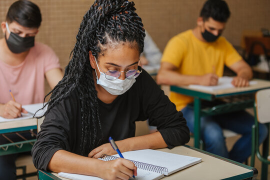 Latin students in the classroom. Female student wearing mask and writing in notebook with a pen. Covid-19. Pandemic.