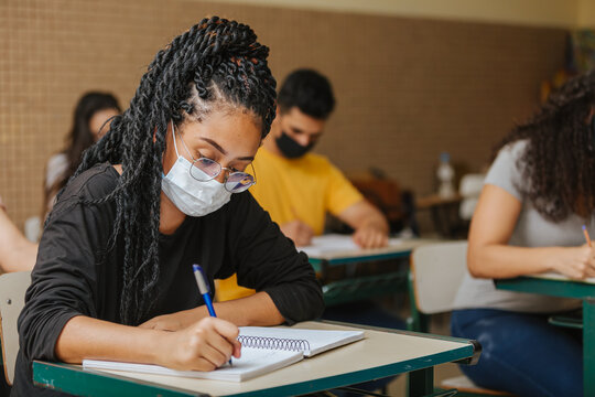 Latin students in the classroom. female student with twisted hair wearing mask and writing in notebook with a pen. Covid-19. Pandemic.