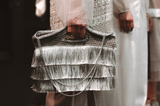 Woman's hand holding a stylish fashionable silver bag made of thread and chain. Fashion Week shot