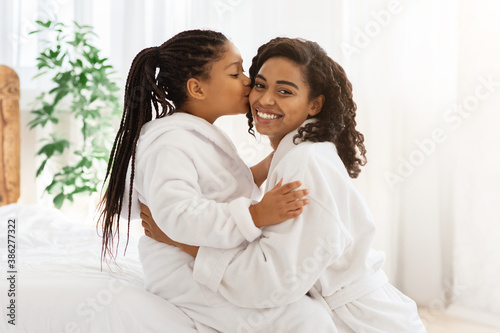 Mother's Day. Adorable Black Little Girl Kissing Mom At Home, Wearing Bathrobes