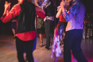 Couples dancing traditional latin argentinian dance milonga in the ballroom, tango salsa bachata lesson in the red lights, dance festival