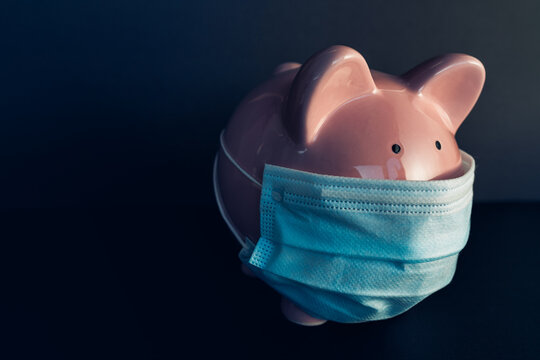 Global economy during coronavirus pandemic. Piggy bank wearing surgical face mask. Financial crisis, banking concept.