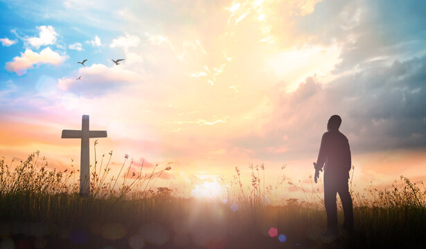 Resurrection of Easter Sunday concept: Silhouette christian over cross meadow sunset background