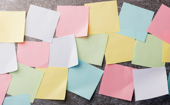 Many blank multicolored paper stick note list on concrete wall background, Business reminder memory post-it notes work today concept