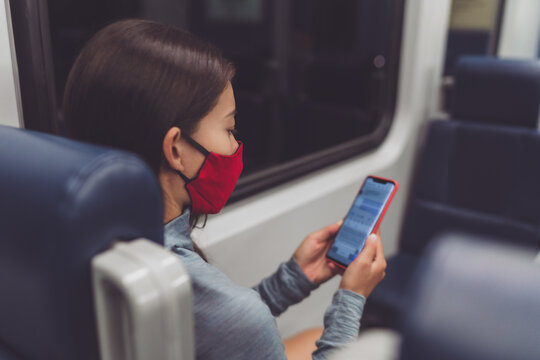 Train commute during corona virus pandemic. Woman passenger using mobile phone wearing face mask sitting in public transport texting online on contact tracing app.