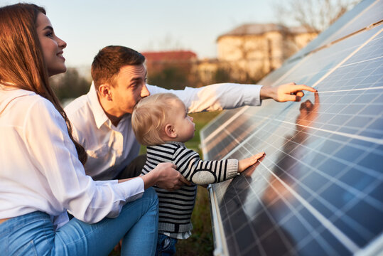 Side close-up shot of a young modern family with a little son getting acquainted with solar panel on a sunny day, green alternative energy concept