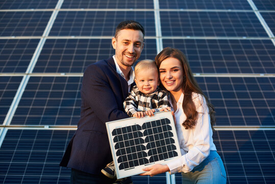 Portrait of a young family holding a small solar panel and a baby boy, smiling and looking at camera. Concept of green generation