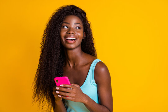 Photo portrait of young curly african american woman holding phone in two hands laughing wearing blue singlet isolated on bright yellow colored background