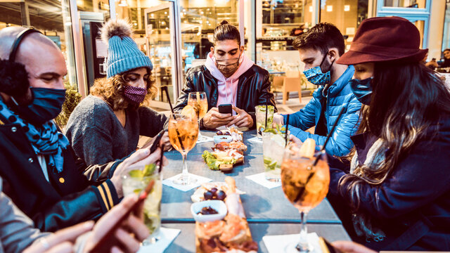 Millennial people wearing face mask using smart phone outdoor - Group of friends sharing content on socia media with cellphone - New normal and technology concept